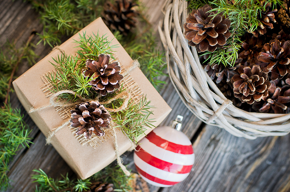 gift decorated with pine cones on the wooden background