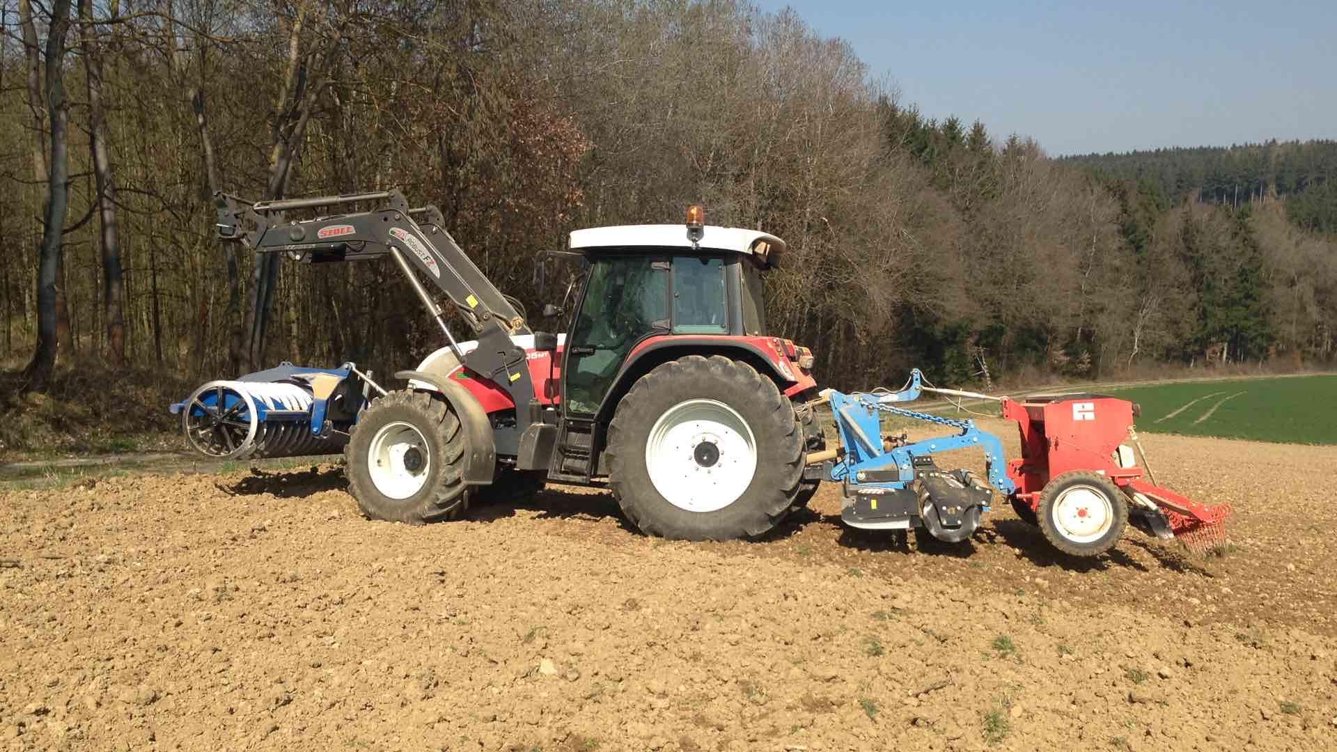 Traktor mit Sähmaschine auf dem Feld