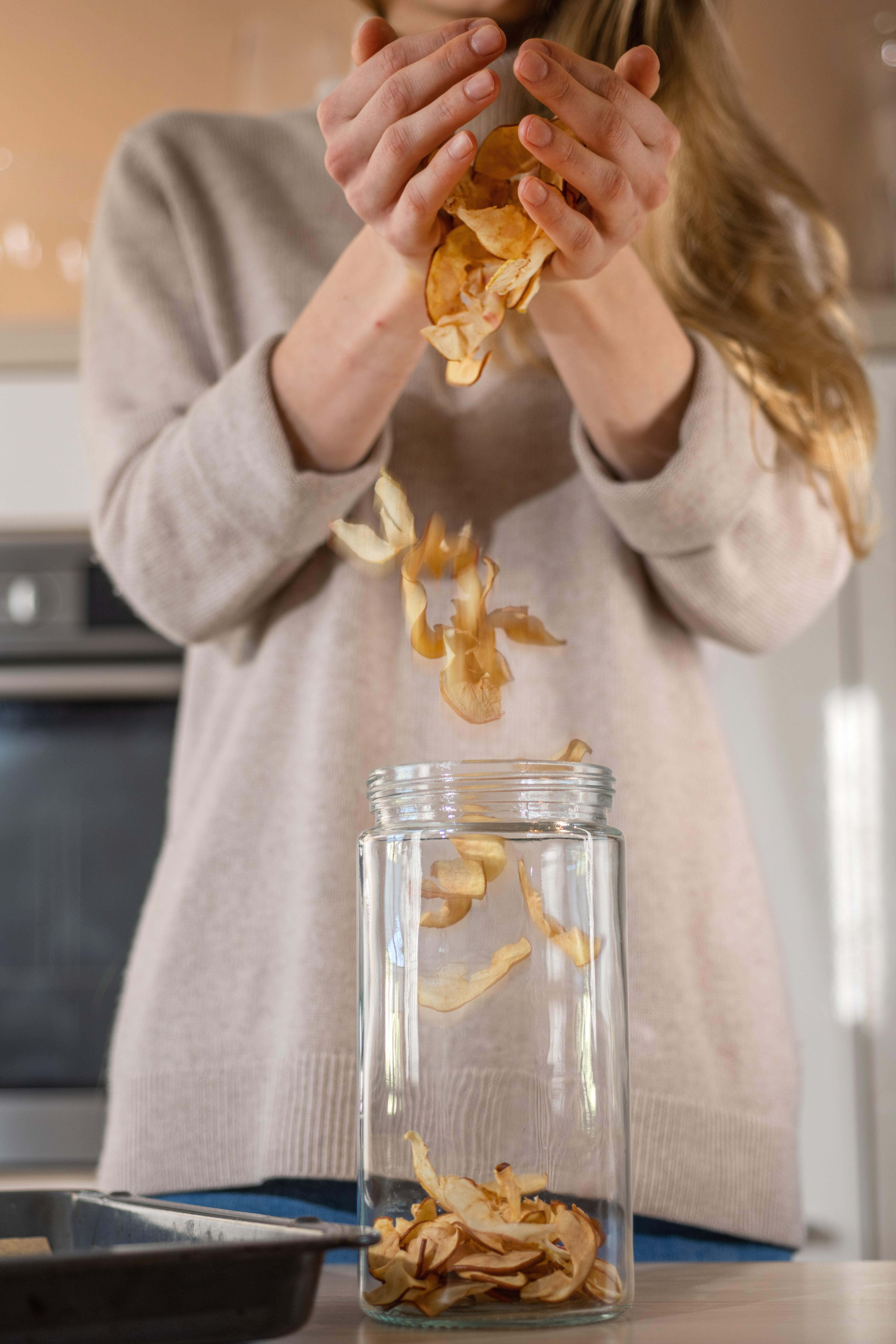 Getrocknete Apfelspalten werden in ein Behältnis gefüllt.