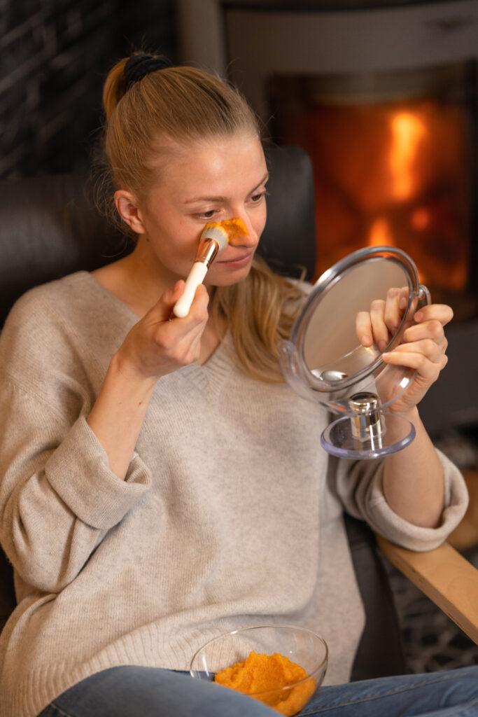 Model Tessa trägt Karottenmaske mit einem Pinsel auf ihr Gesicht auf