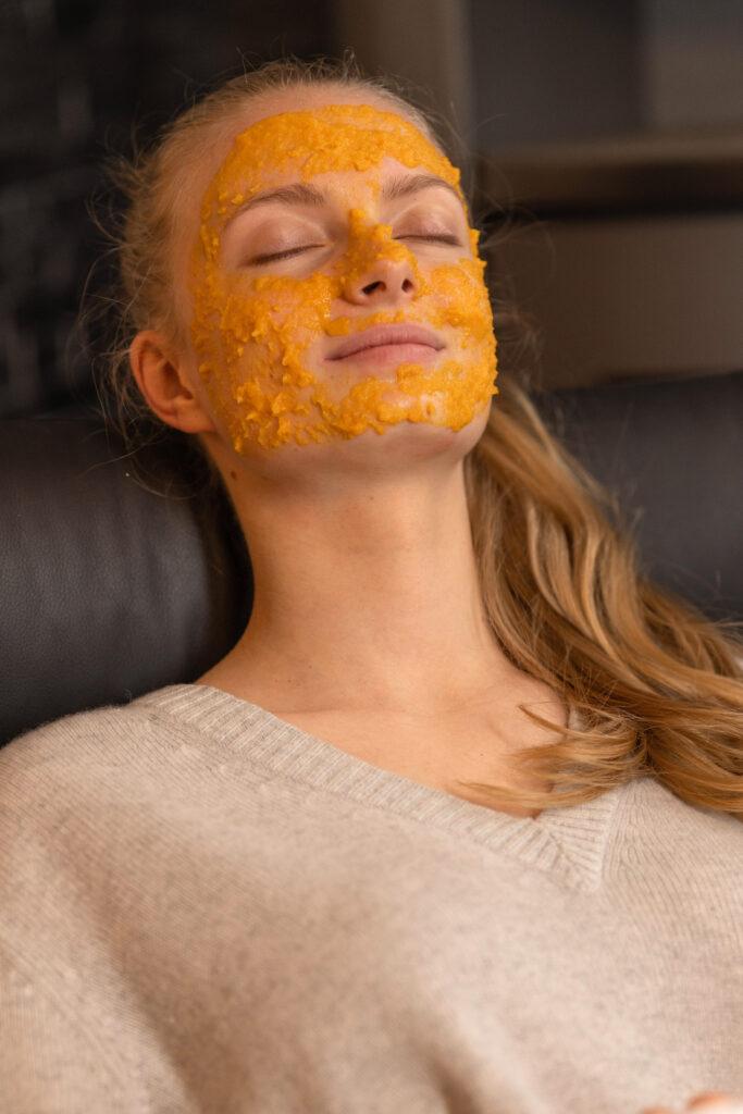 Model Tessa liegt entspannt mit einer Karottenmaske im Gesicht mit geschlossenen Augen im Sessel