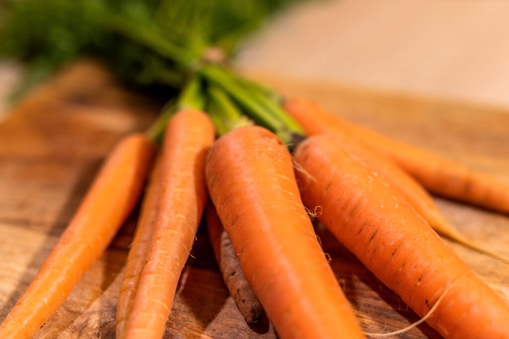 Ein Bund Karotten liegt auf einem Holzbrett