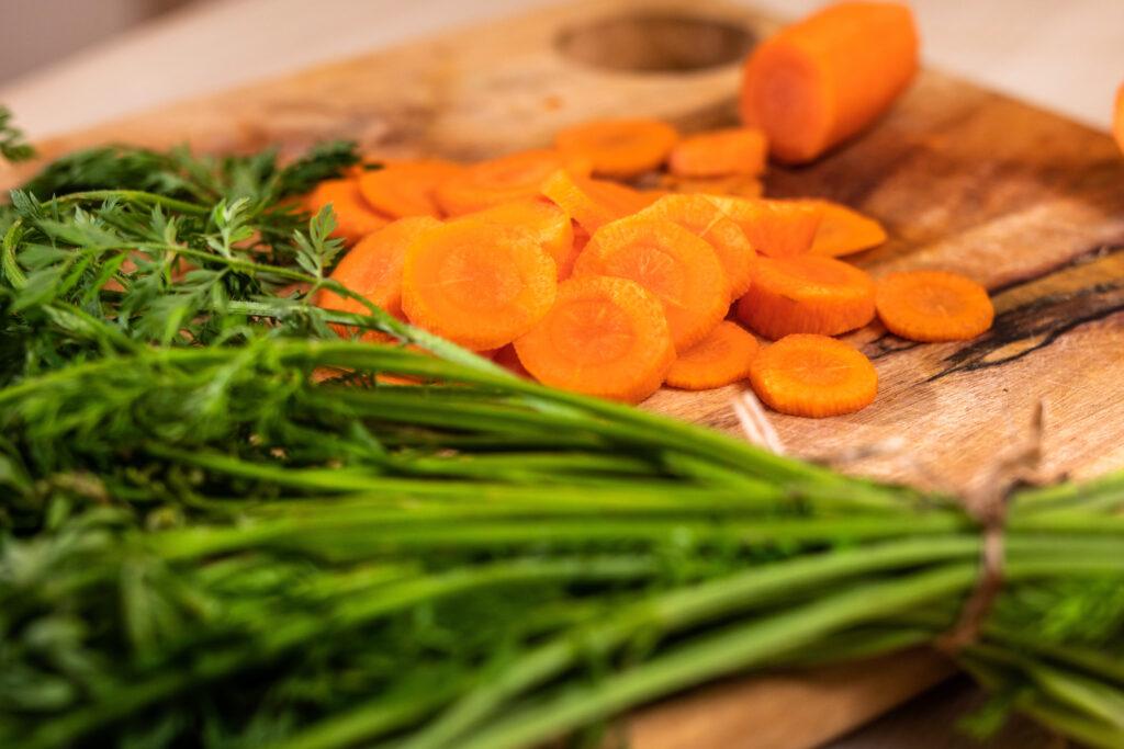 Geschnittene Karotten mit Grün liegen auf einem Holzbrett