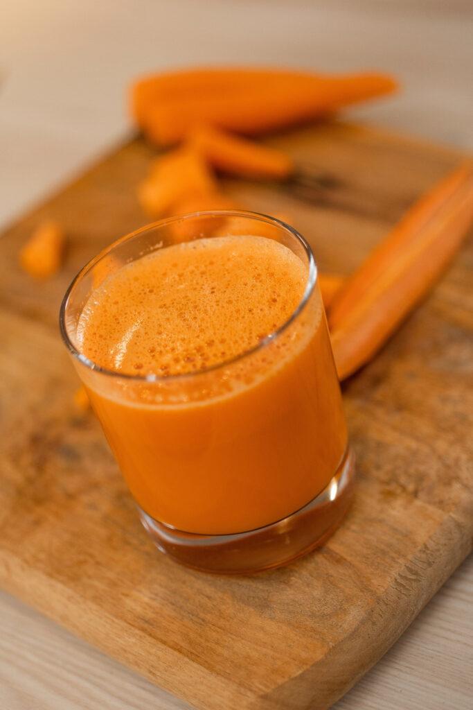Karottensaft im Glas steht auf einem Schneidebrett