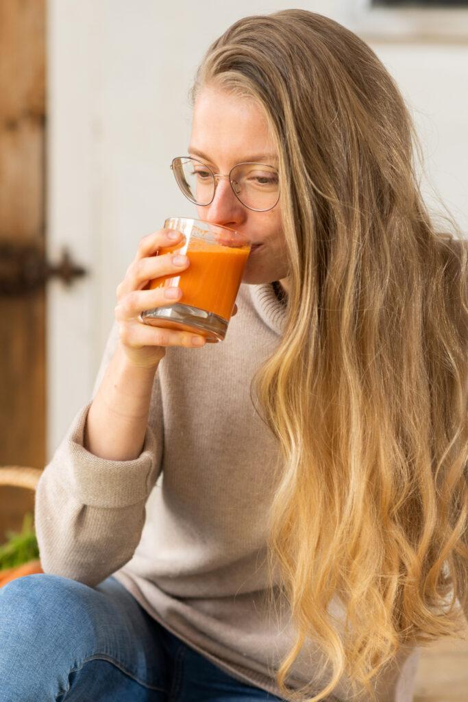 Model Tessa trinkt einen Schluck Karottensaft