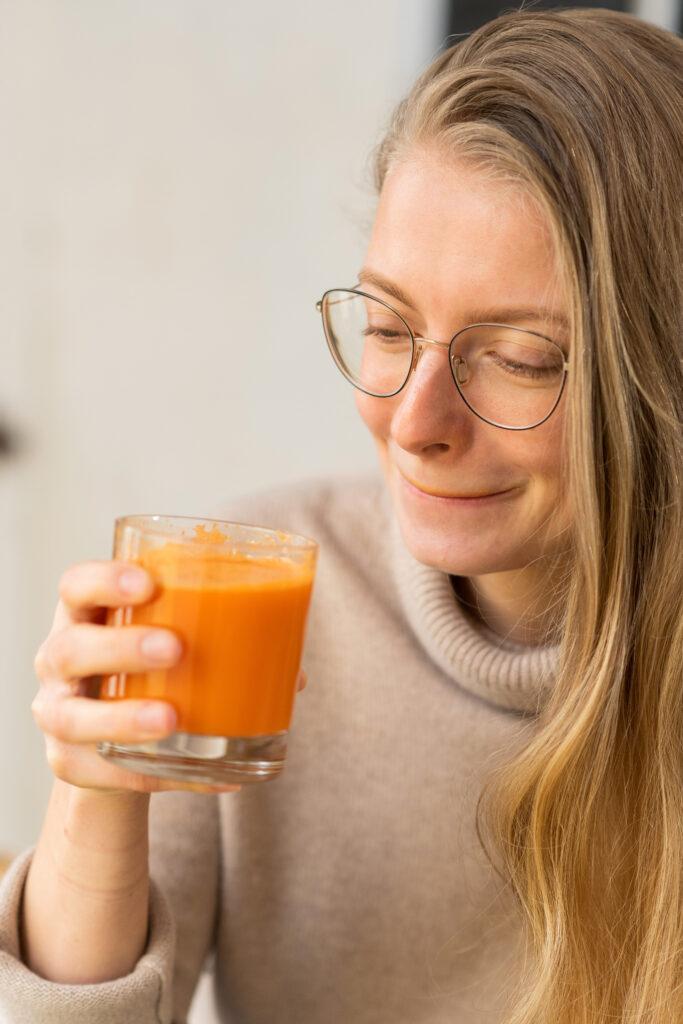 Model Tessa hält dsa Glas mit Karottensaft und leckt sich über die Lippen