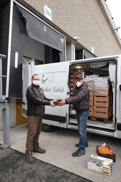 Unser Engagement für mehr Lebensmittelwertschätzung: dennree Mitarbeiter übergibt Lebensmittel an Ehrenamtliche der Tafel