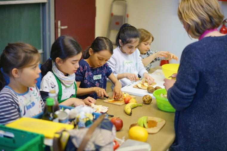 Unser Engagement für mehr Lebensmittelwertschätzung: Bei einer Veranstaltung von Restlos Glücklich schnippeln Kinder Obst und Gemüse.