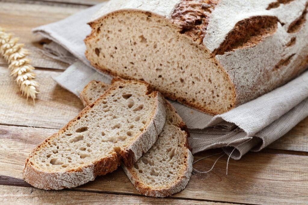Ein Laib Brot und einige aufgeschnittene Scheiben liegen auf einem Holztisch.